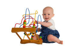 Happy baby with educational toy. Happy cute baby playing on the floor with a wooden educational toy with looped wires for teaching coordination and colours Stock Images
