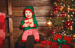 Happy baby elf helper of Santa with gift at christmas tree Royalty Free Stock Image