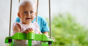 Happy baby enjoying outdoor activities and smiling while swinging royalty free stock photo