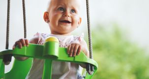 Happy baby enjoying outdoor activities and smiling while swinging stock image