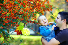 Happy baby and father having fun in colorful park Stock Photos