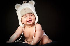 Happy baby in fun cap. Ower black background Stock Images