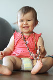 Happy baby girl. Baby girl sitting on the floor and playing with mom's beads Stock Photo