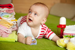 Happy baby girl. With heap of baby's things Stock Photography