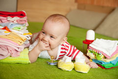 Happy baby girl. With heap of baby's things Royalty Free Stock Image
