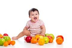 Happy baby girl. Sitting among fresh fruits Royalty Free Stock Image