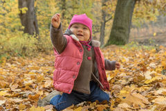 Happy baby girl in autumn park on fall day Royalty Free Stock Photo