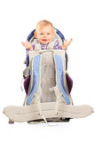 Happy baby girl in a baby carrier for hiking. On white background Royalty Free Stock Images