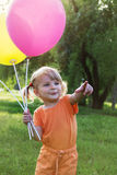 Happy baby girl with balloons among meadow Stock Photos