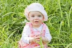 Happy baby girl with blue eyes. Lying on grass stock images