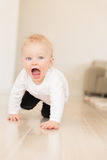Happy baby girl with blue eyes crawling on the ground. Stock Photography