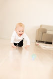 Happy baby girl with blue eyes crawling on the ground. Royalty Free Stock Images