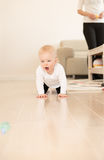 Happy baby girl with blue eyes crawling on the ground. Royalty Free Stock Image