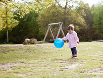Happy baby girl chasing the ball in the park Royalty Free Stock Images