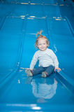 Happy baby girl on colorful slide Stock Photo
