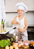 Happy baby girl in cook hat cooking soup Royalty Free Stock Image