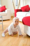 Happy baby girl crawling on a hardwood floor. Happy eight month old baby girl crawling on a hardwood floor in living room royalty free stock image