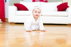 Happy baby girl crawling on a hardwood floor. Happy eight month old baby girl crawling on a hardwood floor in living room royalty free stock photos
