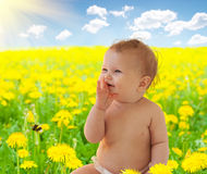 Happy baby-girl among dandelions in Spring Stock Photo
