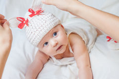 Happy baby girl dressed in knitted bunny costume Stock Images
