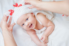 Happy baby girl dressed in knitted bunny costume Stock Photo