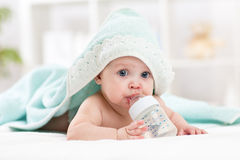 Happy baby girl drinks water from bottle wrapped towel after bath Royalty Free Stock Images