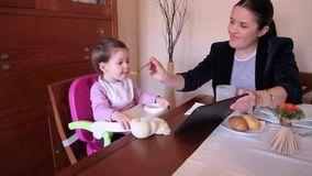 Happy baby girl eating and watching electronic tablet stock video footage