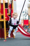 Happy baby girl enjoying a swing ride on a playground Royalty Free Stock Images