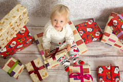 Happy baby girl with gift boxes. Little girl being happy ,sitting on gift box and smiling.She is  surrounded by more gift boxes Royalty Free Stock Photography