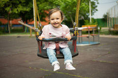 Happy baby girl is giving in swing Stock Image