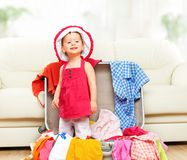 Happy baby girl is going on trip, pack suitcase Stock Photos