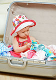 Happy baby girl is going on trip, pack suitcase Royalty Free Stock Photography
