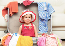 Happy baby girl is going on trip, pack suitcase. Happy baby girl is going on a trip, pack a suitcase Royalty Free Stock Photos
