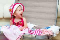 Happy baby girl is going on trip, pack suitcase Royalty Free Stock Images