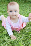 Happy baby girl on grass. Happy baby girl lying on grass royalty free stock images