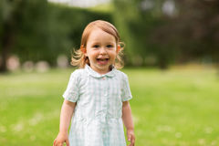 Happy baby girl on green summer field Royalty Free Stock Image