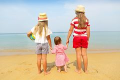 Happy baby girl and her sisters playing in sand on a beautiful beach stock photography