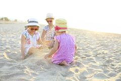 Happy baby girl and her sisters playing in sand on a beautiful beach stock photos