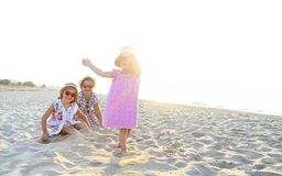 Happy baby girl and her sisters playing in sand on a beautiful beach royalty free stock image
