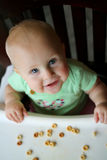 Happy Baby Girl in High Chair Eating Cereal Stock Photos
