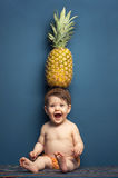 Happy baby girl holding a pineapple over her head Stock Photo