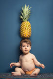 Happy baby girl holding a pineapple over her head Royalty Free Stock Photos