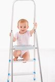 Happy baby girl on ladder Royalty Free Stock Photography