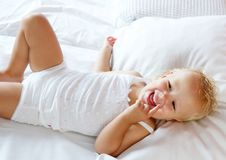 Happy baby girl laughing in bed Royalty Free Stock Images