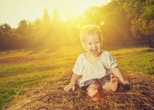 Happy baby girl laughing on hay in summer Royalty Free Stock Image