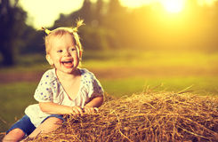 Happy baby girl laughing on hay in summer. At sunset Stock Photos