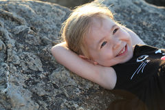 Happy baby girl lie in the sun on the stone near the sea Royalty Free Stock Images