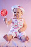 Happy baby girl lollipop. Play playful small red pink eat Stock Image