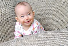 Happy baby girl looking up and smiling. Happy, healthy, energetic, loved and expressive baby girl smiling between pillows and looking up Stock Image