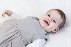 Happy baby girl lying on back Stock Images
